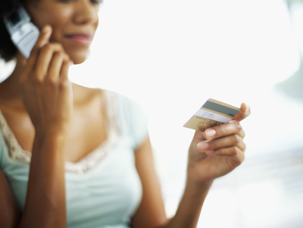 young woman talking on a mobile phone and holding a credit card