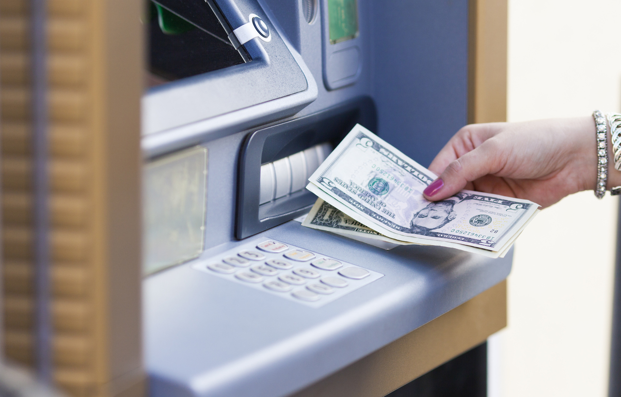 A female hand taking dollar bills out of an ATM