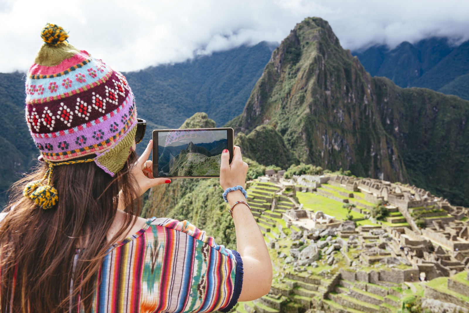 Peru, woman taking pictures of Machu Picchu citadel and Huayna Picchu mountain with a tablet